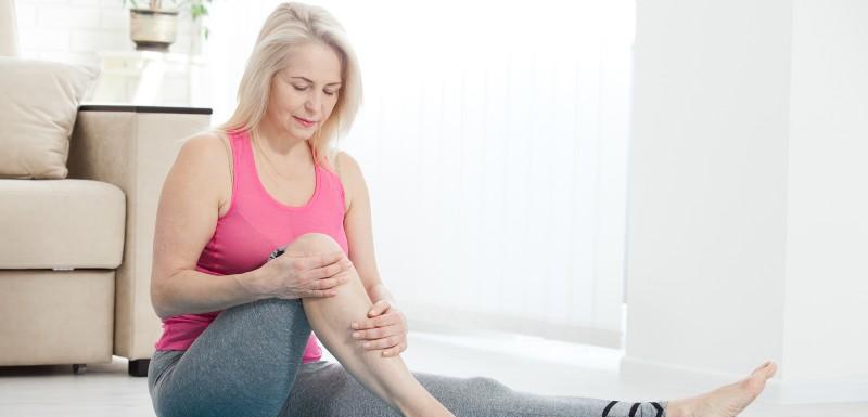 Femme assise par terre le genou pliée, les mains dessus